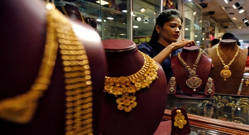 Salesperson attends to customer, inside a jewellery showroom during Akshaya Tritiya, a major gold-buying festival, in Mumbai